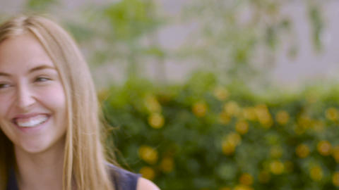 Portrait of a cute blond teenage girl smiling and laughing at the camera Footage
