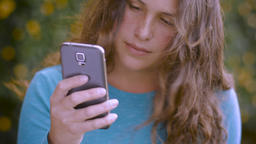 A young attractive woman looks at her cell phone and pulls her hair back Footage