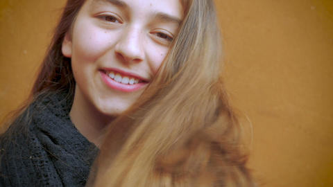A beautiful young teenage girl twirls her lovely long brunette hair and smiles i Footage