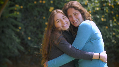 Two beautiful teenage girl friends with long brunette hair hug, smile and laugh Footage