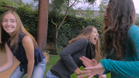 Hand held of three teenage girls dancing outside having fun and one falls to the Footage