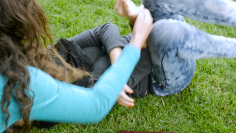 A young teenage girl is tickled and laughing while lying and rolling around on t Footage