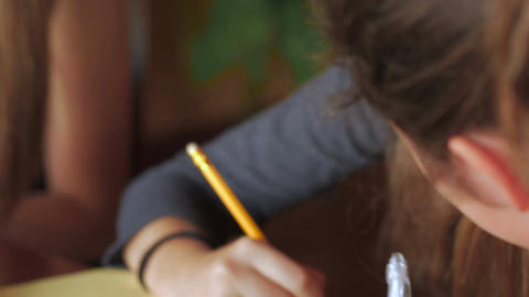 Tilt up close up of beautiful young teenage girls writing with pens and pencils  Footage