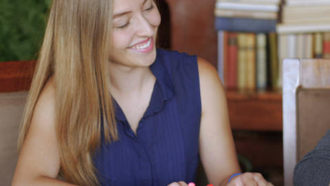 Push in of a happy cute teenage girl doing her homework at her modern house Footage