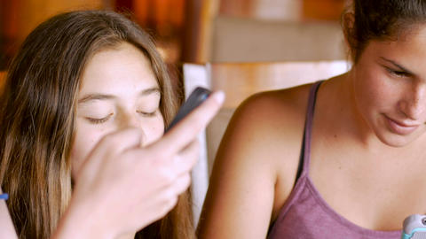 Close up of attractive teenage girls sharing their smart phones and tablets toge Footage