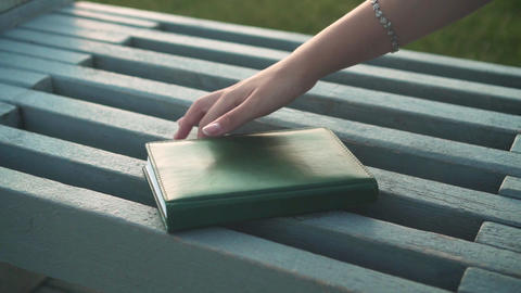 Close-up of a notebook lying on a bench. Female hand takes a notebook Live Action