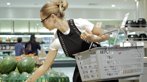 Young woman making choice in grocery store with fruits Live Action