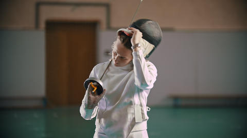 A young woman fencer with long blonde hair takes off a protective helmet Footage