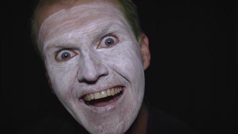 Clown Halloween man portrait. Close-up of an evil clowns face. White face makeup Live Action