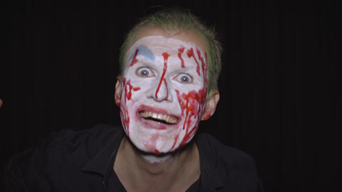 Clown Halloween man portrait. Creepy, evil clowns blood face. White face makeup Live Action