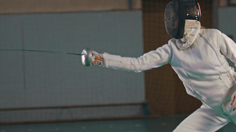 Two young women fencers in protective suits having a training in the gym - make Footage