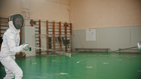 Two young women in protective white costumes at fencing training in the school Footage