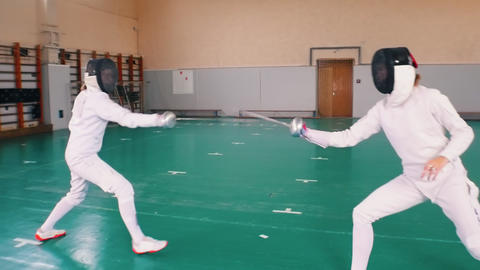 Two young women in white protective suits having a fencing training in the Footage