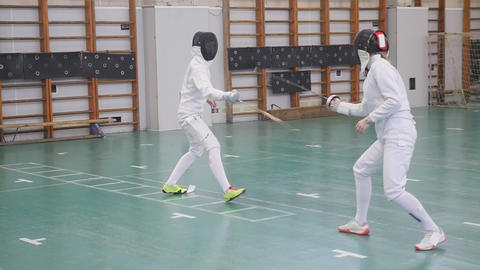 Two young women in full protection having an active fencing training in the Footage