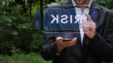 Businessman uses hologram with text Risk Live Action