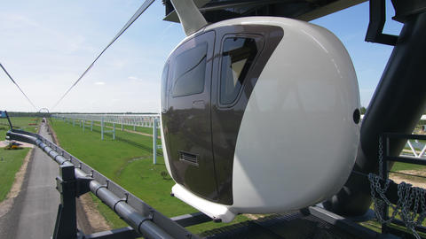 uniwind transport drives along cableway over green meadow Live Action