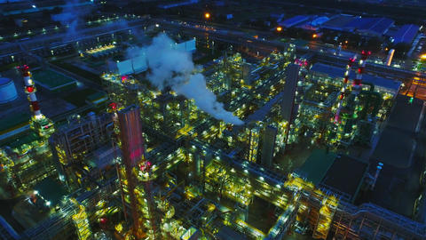 gas and oil refinery complex evening illumination aerial Footage