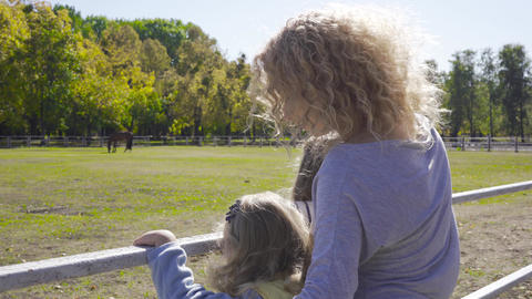 Attractive blond curly woman and two little girls standing next to the corral Footage