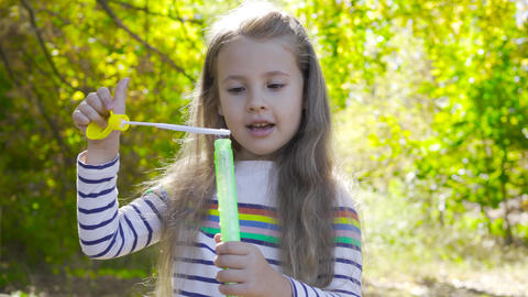 Little brunette girl staying in autumn sunrays and blowing soap bubbles. Little Footage