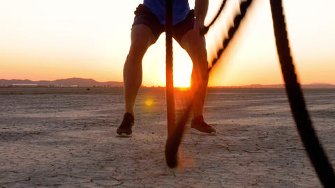 Athletic man working out with battle ropes on a dry lake at sunset Footage