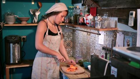 Woman cutting raw fresh carrot on chopping board Footage