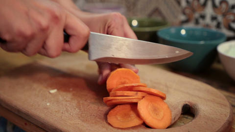 Woman hands slicing carrot on cutting board Footage