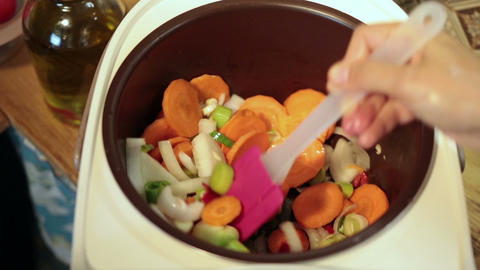 Woman hands stirring vegetables in Multicooker Live Action