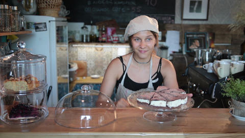 Smiling waitress showing a fresh tasty cheesecake Live Action