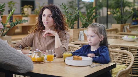 positive woman talks with family sitting at table in cafe Footage