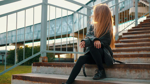 Teenager girl in black leather jacket sitting on stairs on urban landscape Footage