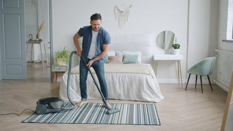 Cheerful man using vacuum cleaner during clean-up at home dancing having fun Live Action