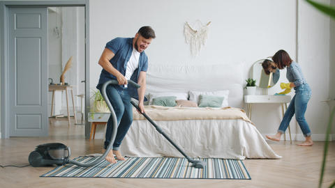 Man and woman having fun during clean-up at home vacuuming and dusting dancing Live Action