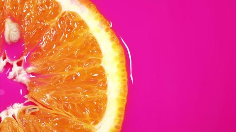 slice orange floats in pink fresh juice. Juicy piece of orange Live Action