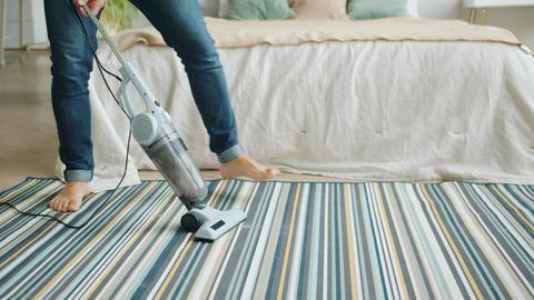 Tilt-up of joyful man vacuuming carpet in apartment pretending to play guitar Footage