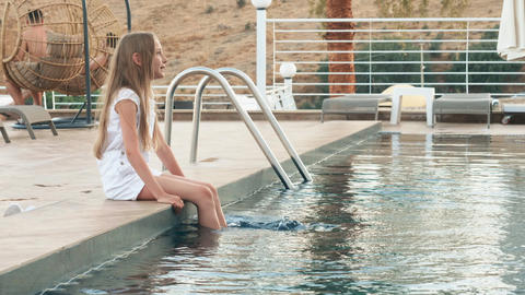 Teenager girl sitting on swimming pool edge dipping legs in water. Happy girl Live Action