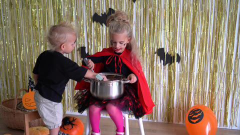 children mix sweets in large pot. Children play on Halloween holiday. 4K GIF