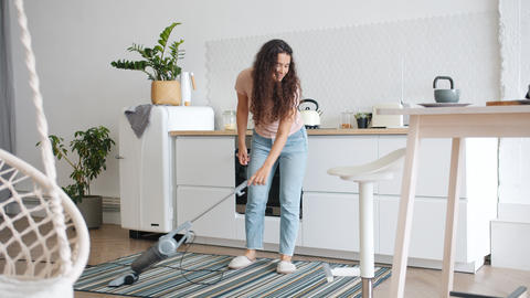 Joyful housewife vacuuming floor in kitchen then dancing relaxing having fun Footage