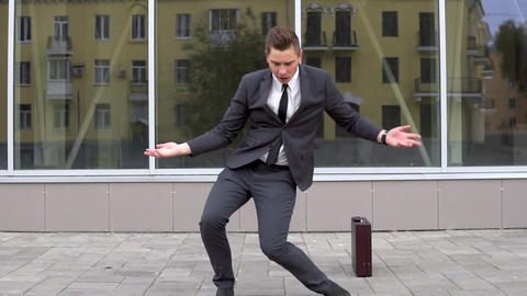 A young businessman in a suit is dancing. Modern youth flex. Background mirror Live Action