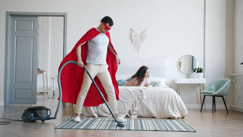 Man in superhero cape vacuuming carpet at home while lady reading book in bed Footage