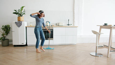 Happy young woman washing floor with mop and dancing at home in kitchen Footage
