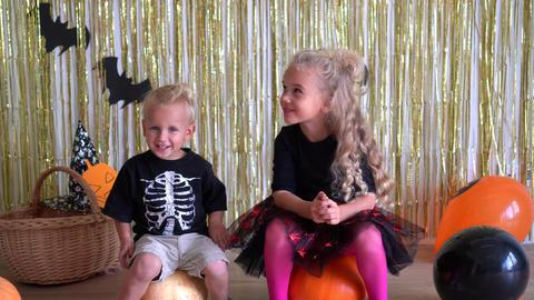 kids joke when they see big Halloween spider. Balloons, pumpkin background. 4K GIF