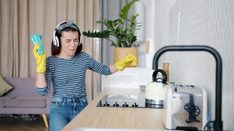 Joyful lady cleaning kitchen then dancing singing enjoying music in headphones Footage