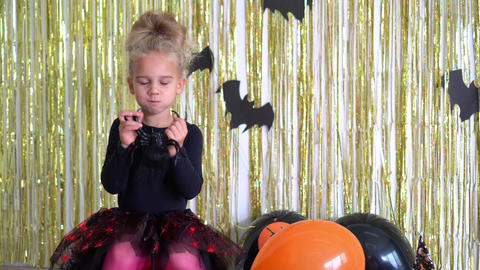 girl witch play with spider toy on pumpkin. Halloween party treat or trick. 4K GIF