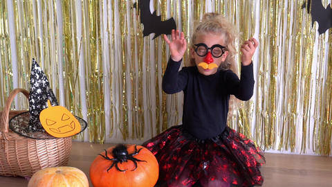 girl with clown glasses waving hands during Halloween celebration GIF