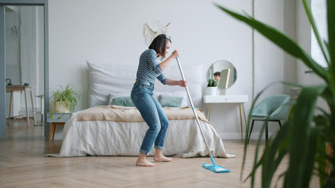 Happy young lady washing floor with mop and dancing at home in bedroom Footage