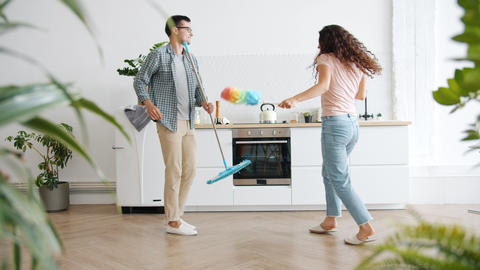 Slow motion of family dancing in kitchen during clean-up with mop and duster Live Action