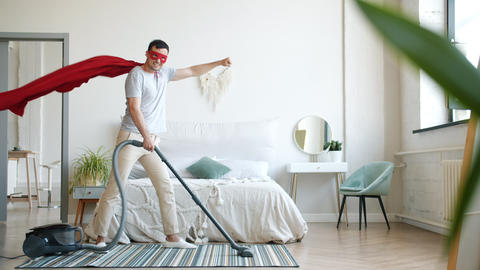 Portrait of smiling superman vacuuming carpet at home and looking at camera Footage