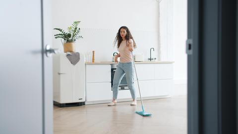 Joyful girl dancing with mop in kitchen singing enjoying music during clean-up Live Action