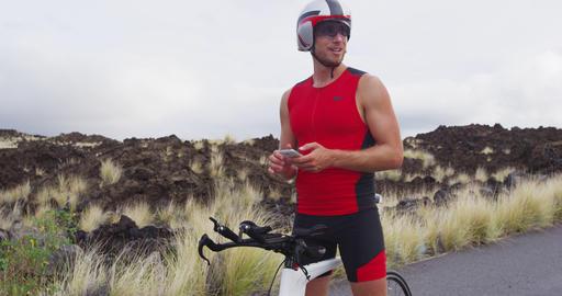Phone app - triathlete man biking on triathlon bike using smartphone apps Live Action