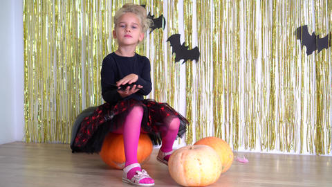 Halloween witch girl hold black spider in hand. pumpkins and horror holiday. 4K GIF